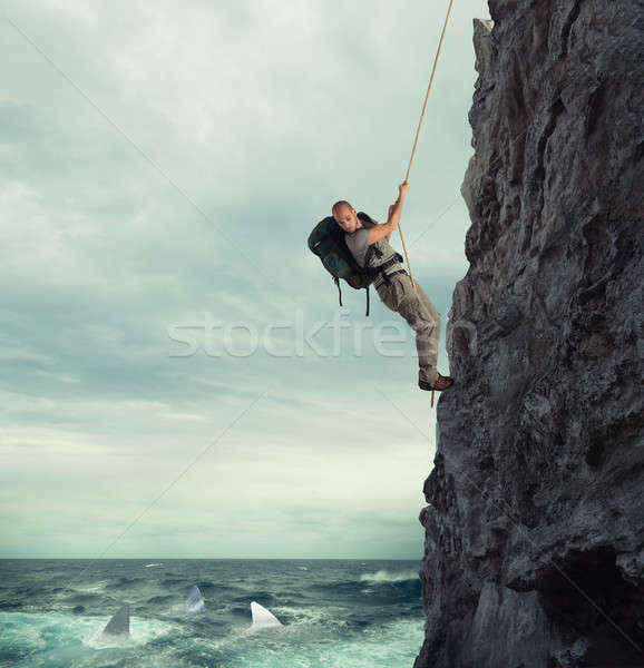 Explorer climbs a mountain with the risk to fall on the sea with sharks Stock photo © alphaspirit