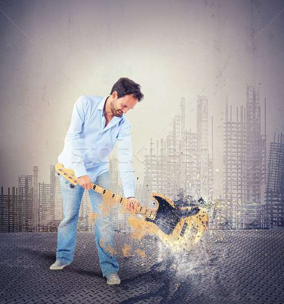 Man musician music rock breaking a guitar Stock photo © alphaspirit