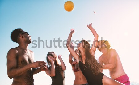 Group of friends playing at beach volley at the beach Stock photo © alphaspirit