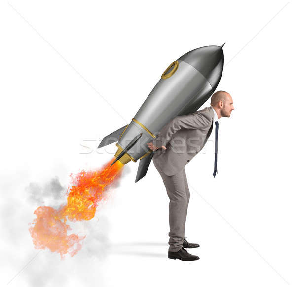 Stock photo: Determination and power businessman that holds a rocket isolated on white background