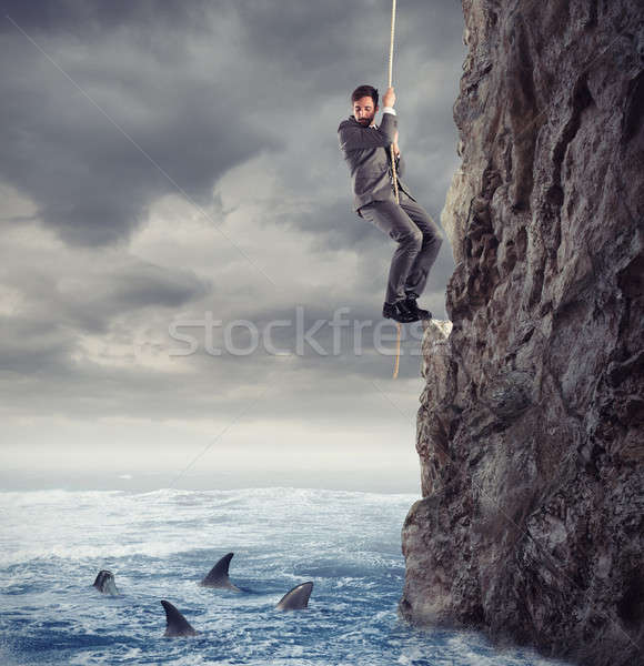 Businessman is likely to fall into the sea with sharks. concept of problems and difficulty in busine Stock photo © alphaspirit