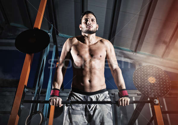 Athletic man works out at the gym with the bar Stock photo © alphaspirit