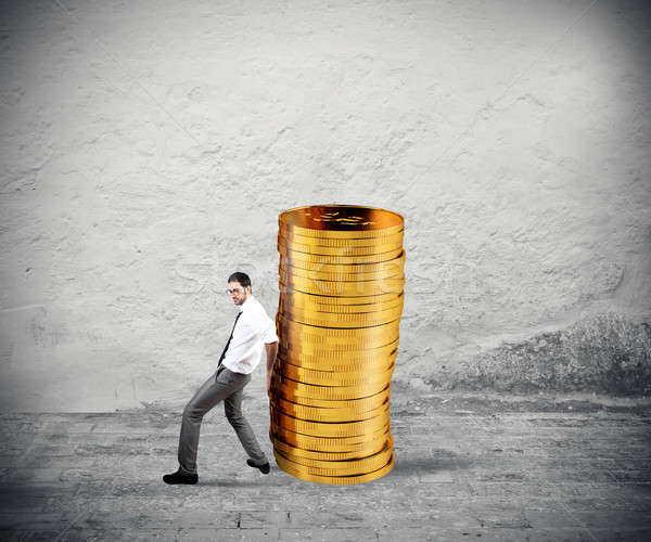Businessman moves a pile of coins. concept of difficulty to saving money Stock photo © alphaspirit