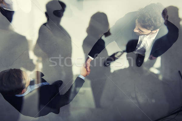 Handshaking business person in office. concept of teamwork and partnership. double exposure Stock photo © alphaspirit