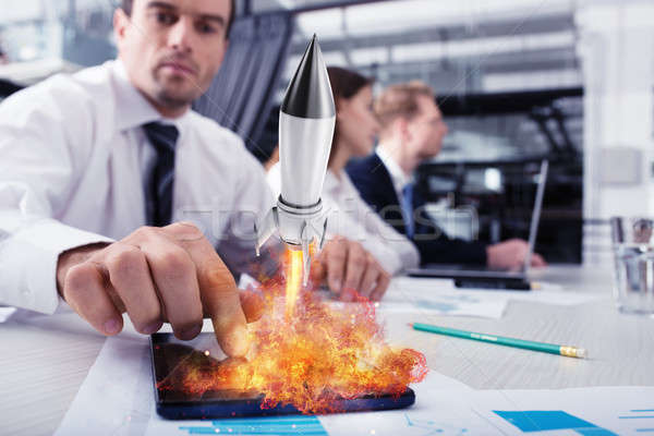Businessperson in office work for a startup of a company with a rocket Stock photo © alphaspirit
