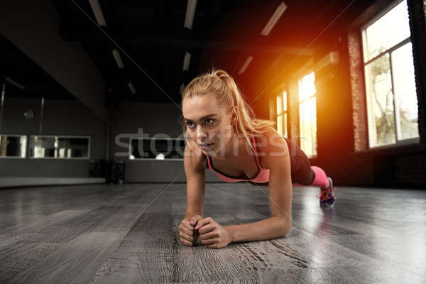 Blonde girl working out at a gym Stock photo © alphaspirit