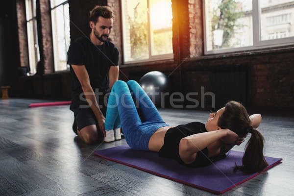 Personal trainer helps a girl with the gym exercises Stock photo © alphaspirit
