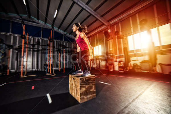 Athletic girl does box jump exercises at the gym Stock photo © alphaspirit