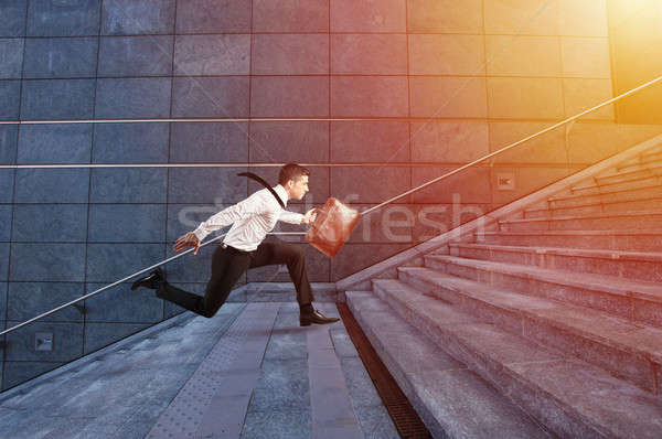 Businessman runs fast over a modern staircase Stock photo © alphaspirit