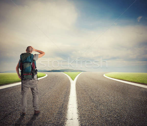 Businessman in front of a crossway must select the right way Stock photo © alphaspirit