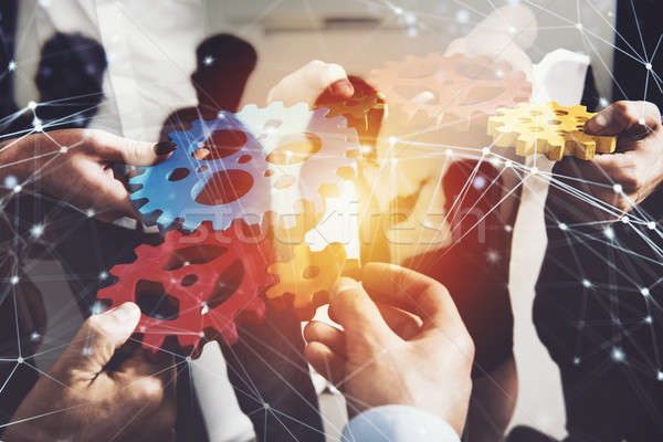 Stock photo: Business team connect pieces of gears. Teamwork, partnership and integration concept. double exposur