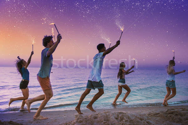 Happy smiling friends running at the beach with sparkling candles Stock photo © alphaspirit