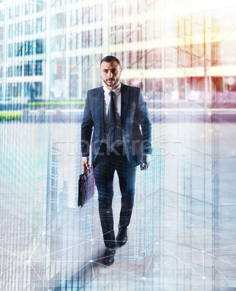 Determinated businessman walking in the city. double exposure Stock photo © alphaspirit