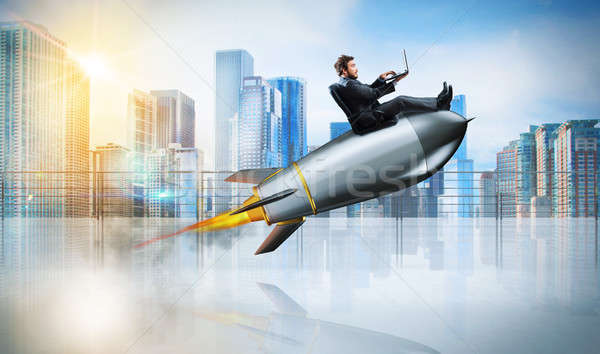 Fast internet concept with a businessman with laptop over a rocket Stock photo © alphaspirit