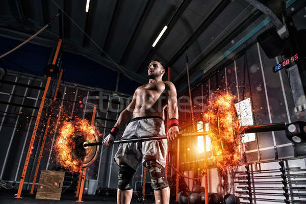Stock photo: Athletic man works out at the gym with a fiery barbell