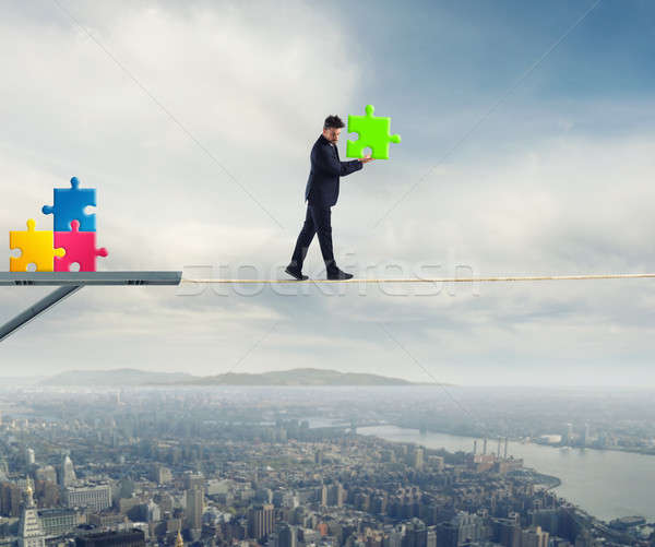Businessman carries a piece of puzzle while he walking on a rope. concept of missing piece Stock photo © alphaspirit