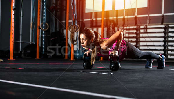 Athletic girl works out at the gym with a kettlebell Stock photo © alphaspirit