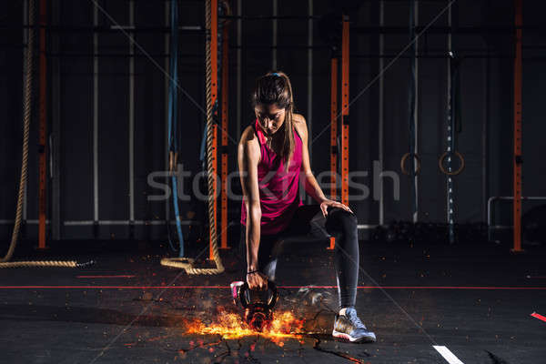 Stock photo: Athletic girl works out at the gym with a fiery kettlebell