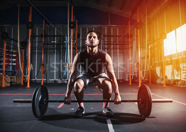 Athletic man works out at the gym with a barbell Stock photo © alphaspirit
