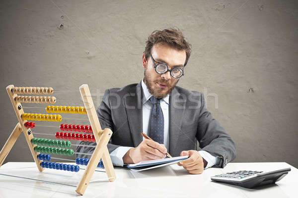 Stock photo: Nerd accountant does calculation of company revenue