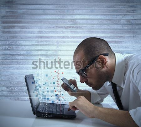 Businessman looks on the computer with a  lens Stock photo © alphaspirit