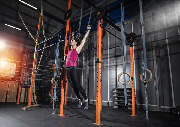 Stock photo: Athletic woman works out at the gym with the bar