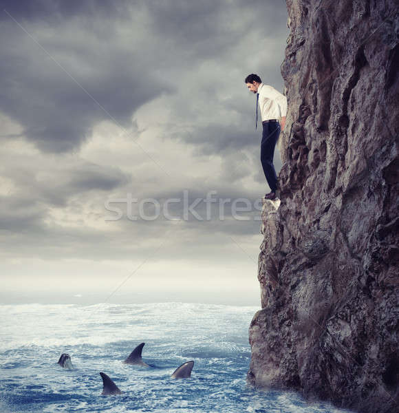 Businessman is likely to fall into the sea with shark. Risks and difficulties concept Stock photo © alphaspirit