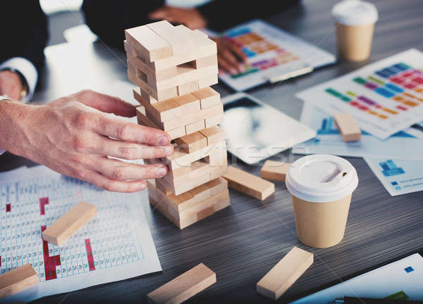 Teamwork of partners. Concept of integration and startup with a small construction of wooden toy Stock photo © alphaspirit