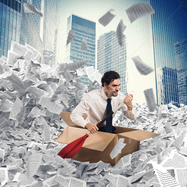 Businessman extricate himself from a sea of paper Stock photo © alphaspirit