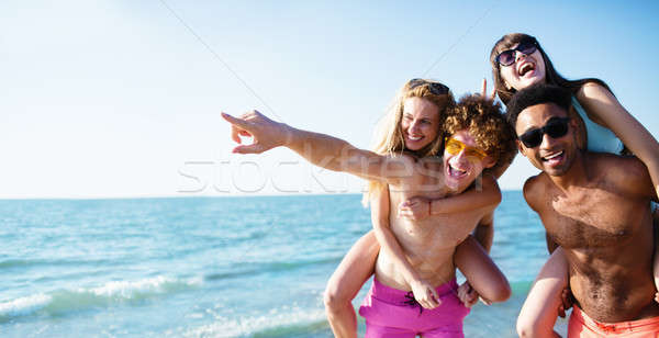 Happy smiling couples playing at the beach Stock photo © alphaspirit