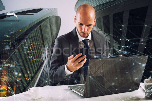Businessman works with smartphone and laptop Stock photo © alphaspirit