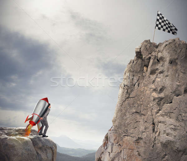 Determination and power businessman that holds a rocket to reach the flag Stock photo © alphaspirit