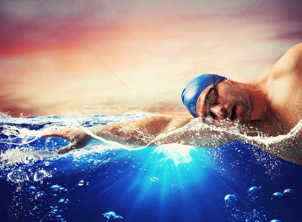 Boy swims in a blue deep water Stock photo © alphaspirit