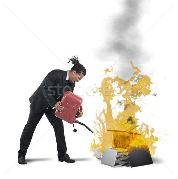 Businessman burns computers Stock photo © alphaspirit