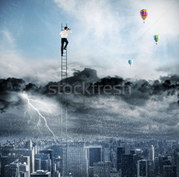 Businessman on a ladder escapes from crisis and looking for a new way Stock photo © alphaspirit