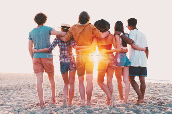 Group of happy friends having fun at ocean beach Stock photo © alphaspirit