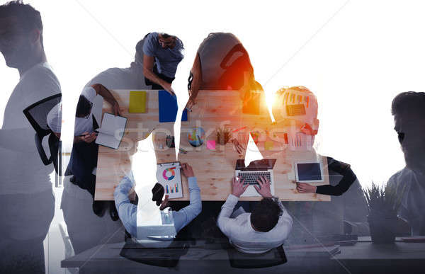 Team of businessmen work together in office. Concept of teamwork and partnership. double exposure Stock photo © alphaspirit