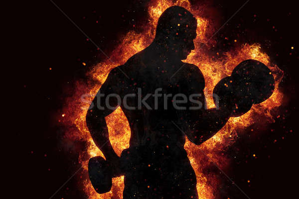 Athletic man training biceps at the gym with fire effect Stock photo © alphaspirit