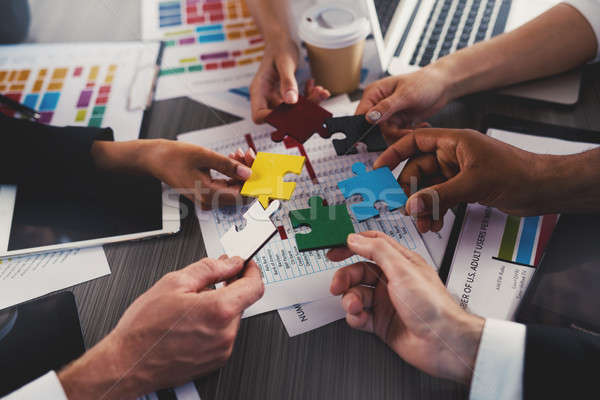 Businessmen building colored puzzles together. Concept of teamwork, partnership, integration and sta Stock photo © alphaspirit