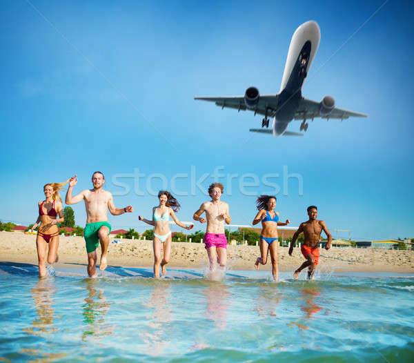 Group of friends run in the sea with aircraft in the sky. Concept of summertime Stock photo © alphaspirit