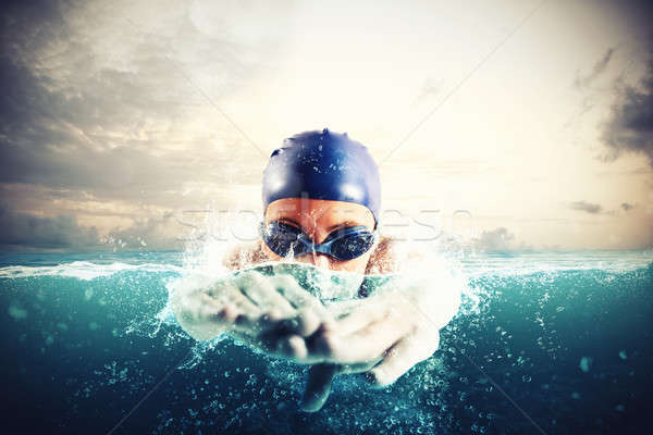 Athlete swims in a blue deep water Stock photo © alphaspirit
