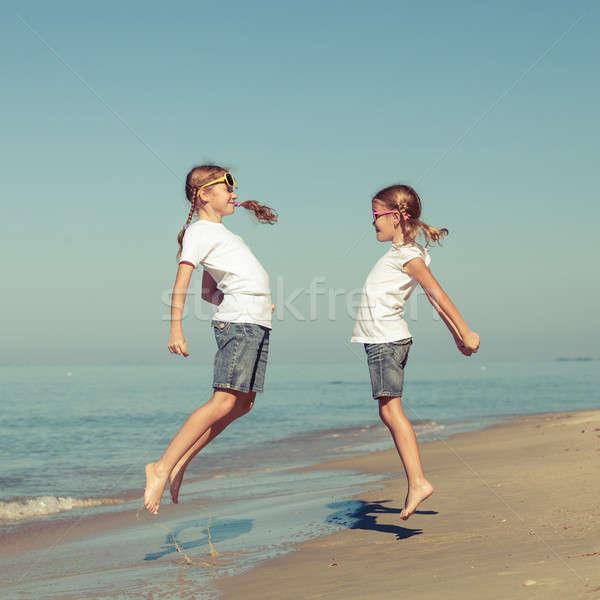 Zwei Schwestern spielen Strand Tag Zeit Stock foto © altanaka