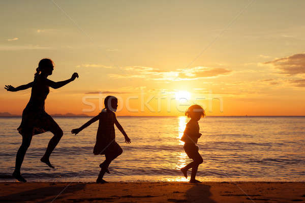 Mother and children standing on the beach at the sunset time. Stock photo © altanaka