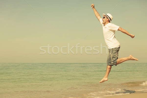 幸せ 男 ジャンプ ビーチ 日 時間 ストックフォト © altanaka