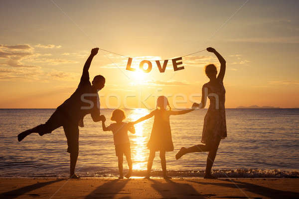 счастливая семья Постоянный пляж закат время родителей Сток-фото © altanaka