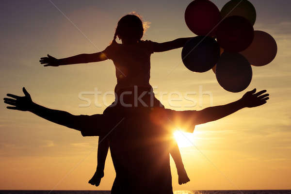 Father and daughter with balloons playing on the beach at the su Stock photo © altanaka