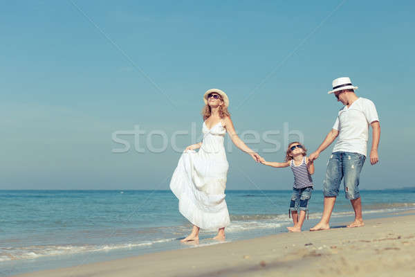 Happy family walking on the beach at the day time.  Stock photo © altanaka