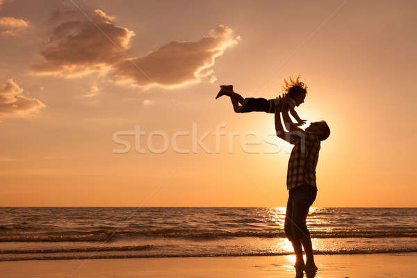 Father and son playing on the beach at the sunset time. Stock photo © altanaka
