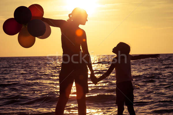 Mother and daughter playing on the beach at the sunset time.  Stock photo © altanaka