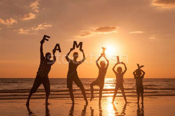 ストックフォト: 幸せな家族 · 立って · ビーチ · 日没 · 時間 · 文字